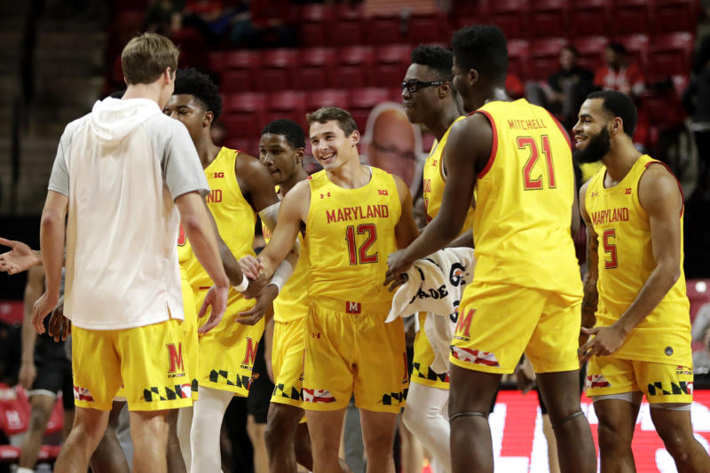 Maryland players swarm guard Reese Mona (12) after he scored his second 3-point shot against the Oakland during the second half of an NCAA college basketball game, Saturday, Nov. 16, 2019, in College Park, Md. Maryland won 80-50. (AP Photo/Julio Cortez)