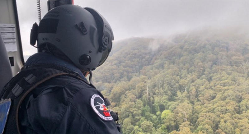 A rescue crew member flies over the NSW crash site - about 27 kilometres inland from Coffs Harbour - in a helicopter.