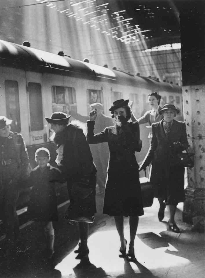 A woman waves her handkerchief goodbye at the station in 'Wartime Terminus, Paddington Station', 1942 (Bert Hardy/ Getty Images)