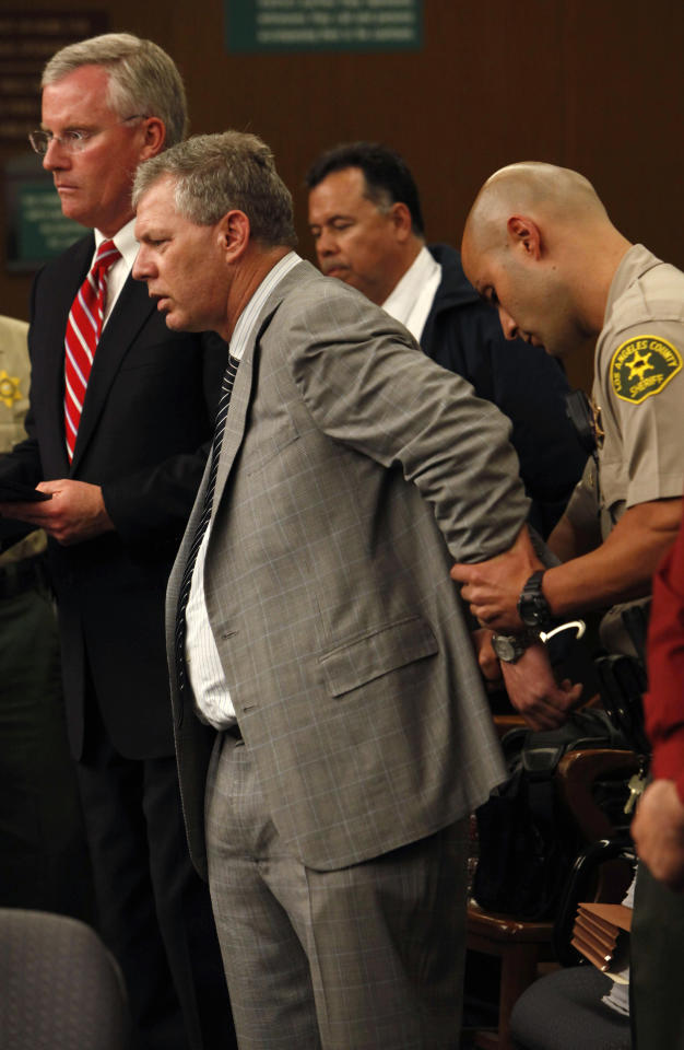 In this Monday, June 6, 2011, photo, Lenny Dykstra, center, is put in handcuffs after his arraignment on grand theft auto and drug possession charges in San Fernando, Calif. Attorney Daniel Nixon is at left. Dykstra, 48, a former New York Mets and Philadelphia Phillies star, was charged with 25 misdemeanor and felony counts of grand theft auto, attempted grand theft auto, identity theft and other crimes, said Jane Robison, a spokeswoman for the Los Angeles County district attorney's office. He faces up to 12 years in state prison if convicted. (AP Photo/Michael Robinson Chavez, Pool)