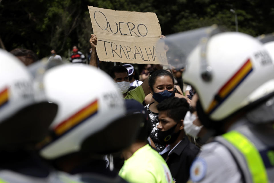 """A demonstrator holds up the Portuguese message """"I want to work"""" outside a city government office where police stand guard during a protest against a two-week-long lockdown to curb the spread of COVID-19 in Brasilia, Brazil, Monday, March 1, 2021. It's the second lockdown in Brasilia since the start of the pandemic one year ago. (AP Photo/Eraldo Peres)"""