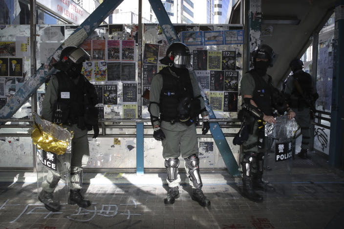Police officers in riot gear gather on a pedestrian overpass during an anti-government protest in Hong Kong, Saturday, Nov. 2, 2019. Defying a police ban, thousands of black-clad masked protesters are streaming into Hong Kong's central shopping district for another rally demanding autonomy in the Chinese territory as Beijing indicated it could tighten its grip. (AP Photo/Kin Cheung)