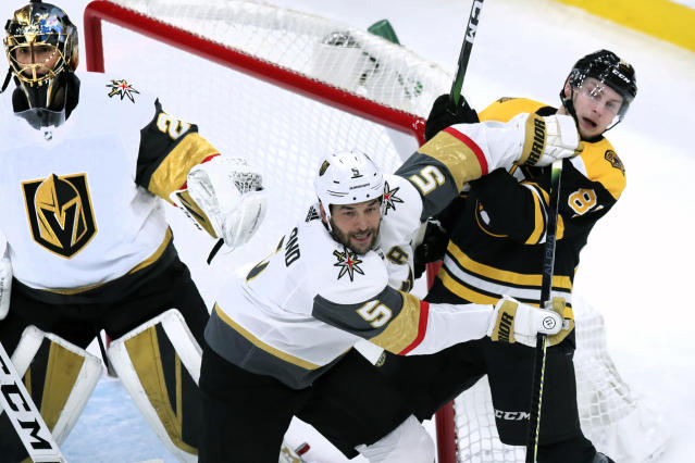 Vegas Golden Knights defenseman Deryk Engelland (5) tries to clear Boston Bruins Anton Blidh, right, away from the goal during the first period of an NHL hockey game in Boston, Tuesday, Jan. 21, 2020. (AP Photo/Charles Krupa)
