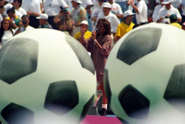 Pop singer Whitney Houston, framed by giant soccer balls, performs during closing ceremonies at the Rose Bowl in Pasadena July 17, 1994 prior to the World Cup final match between Brazil and Italy. Italy and Brazil last played in a World Cup final in 1970, with Pele leading the Brazilians to a 4-1 victory. REUTERS/Gary Hershorn
