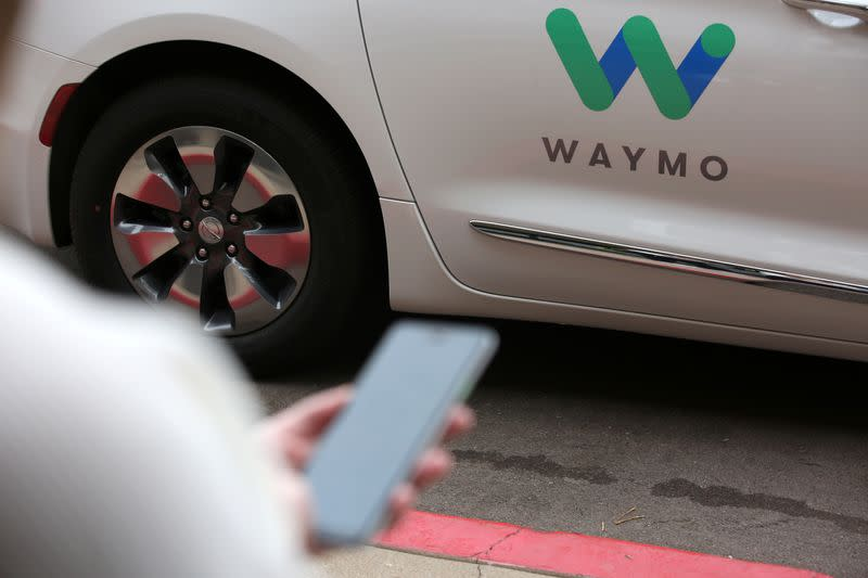 A Waymo employee hails a ride on their phone during a demonstration in Chandler, Arizona