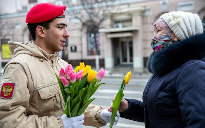 A member of Russia's Young Army Cadets National Movement gives flowers to a woman for International Women's Day  - Erik Romanenko\\TASS via Getty Images