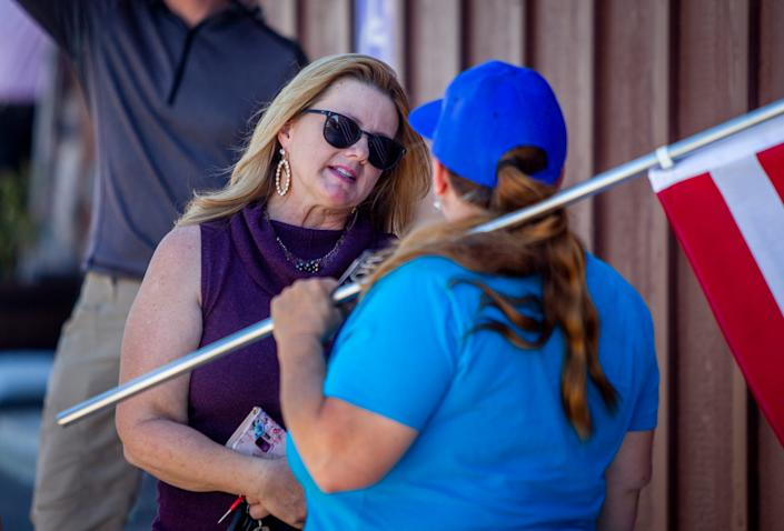 Republican state Rep. Kelly Townsend speaks with a protester after a protest against Gov. Ducey's delay to reopen some businesses on May 1, 2020, in Apache Junction.