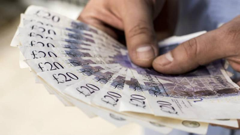 A person holding onto a fan of twenty pound notes
