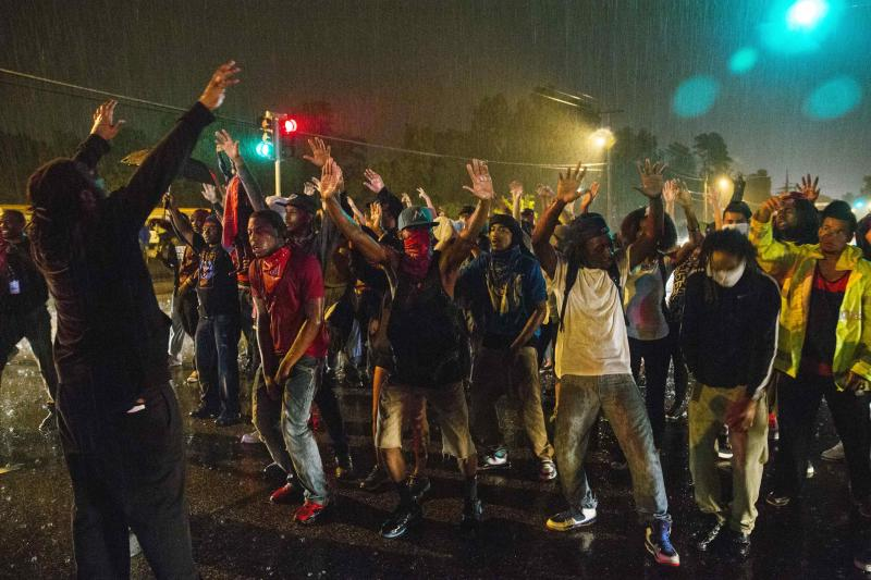 Protesters gesture as they stand in a street in defiance of a midnight curfew meant to stem ongoing demonstrations in reaction to the shooting of Michael Brown in Ferguson, Missouri August 17, 2014. The group of protesters angry at the shooting death of Brown, a black teenager, by a white police officer remained on the streets of Ferguson, Missouri, early on Sunday minutes past the declared curfew, as police began to clear the streets in a tense standoff. REUTERS/Lucas Jackson (UNITED STATES - Tags: CIVIL UNREST CRIME LAW)