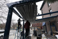 Workers adjust a retractable awning above an outdoor seating area at El Habanero restaurant, Wednesday, Dec. 16, 2020 in the Brooklyn borough of New York. The city is bracing for a severe snowstorm. (AP Photo/Mark Lennihan)