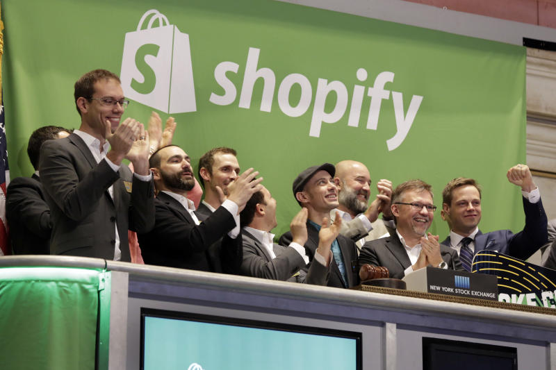 Shopify CEO Tobias Lutke, center wearing hat, is celebrated as he rings the New York Stock Exchange opening bell, marking the Canadian company's IPO, Thursday, May 21, 2015. Shopify Inc. works with merchants who want to offer their own online checkout services, providing a platform for small- and mid-size businesses that sell products online. (AP Photo/Richard Drew)