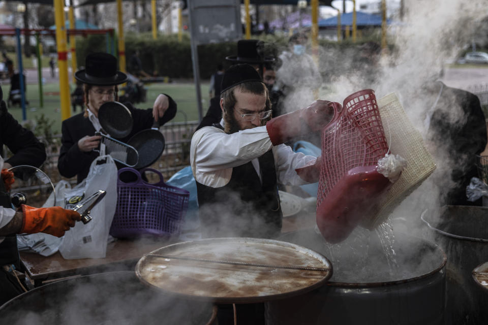 An ultra-Orthodox Jewish man dips cooking utensils in boiling water to remove remains of leaven in preparation for the upcoming Jewish holiday of Passover in Ashdod, Israel, Thursday, March 25, 2021. Israelis will once again hold large family gatherings this weekend to celebrate Passover, the festive Jewish holiday recalling the biblical flight of the Israelites from Egypt. That's thanks to a highly successful coronavirus vaccination campaign that has inoculated 80% of the country's adult population. (AP Photo/Tsafrir Abayov)