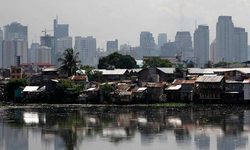 a slum in front of highrises in Manila