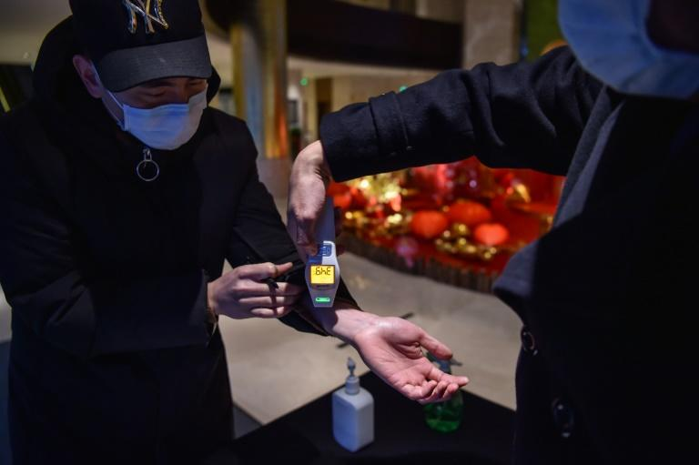 A hotel employee takes the temperature of a person that just arrived at the premise in Wuhan