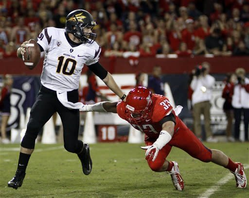 Arizona State starting quarterback Keelan Johnson (10) avoids the attempted tackle by Arizona's Jake Fischer (33) during the first half of an NCAA college football game at Arizona Stadium in Tucson, Ariz., Friday, Nov. 23, 2012. (AP Photo/Wily Low)