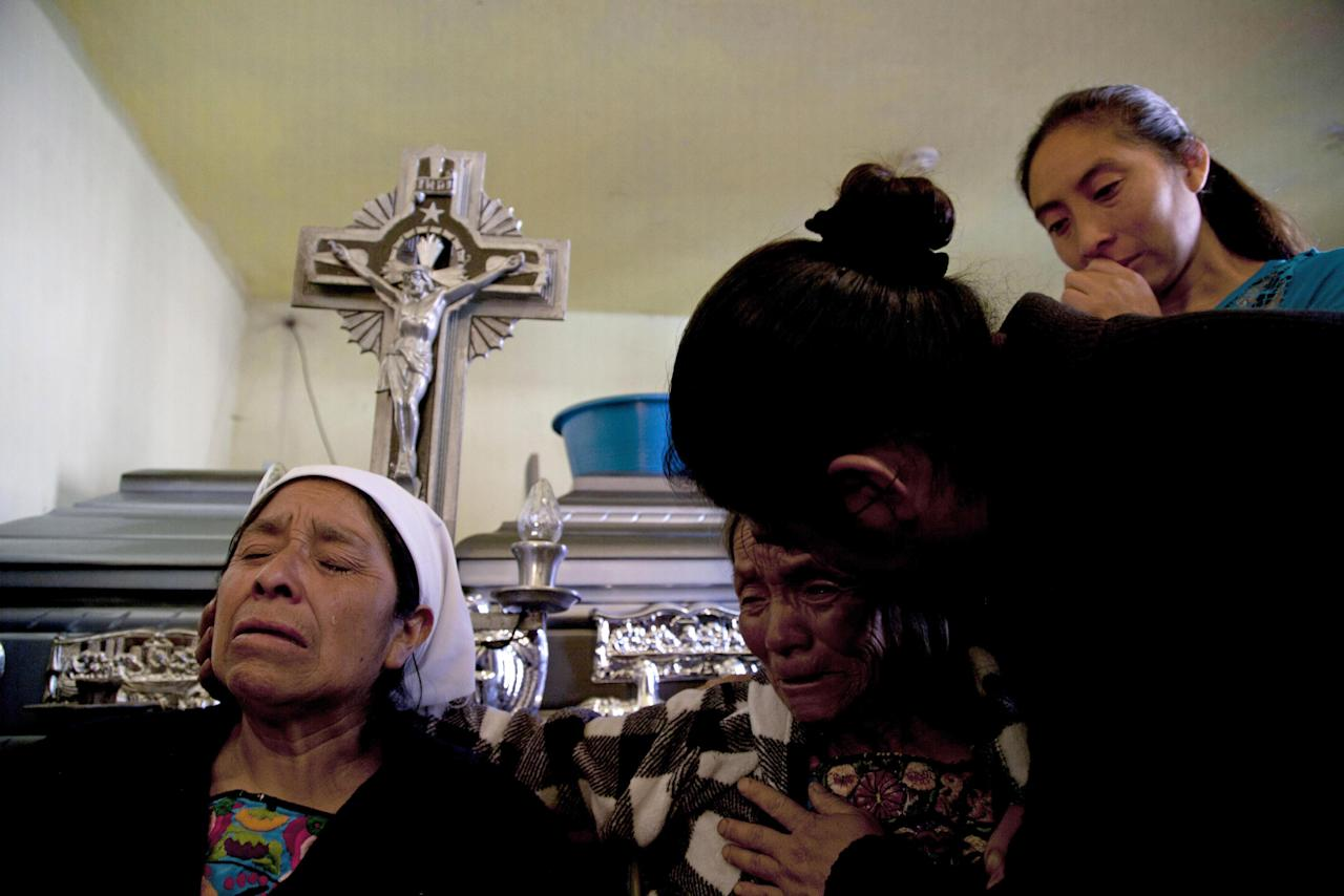 Relatives mourn during a funeral service for members of the Vasquez family who were buried alive when their house collapsed during an earthquake in San Cristobal Cucho, Guatemala, Thursday, Nov. 8, 2012. The family died when a magnitude 7.4 earthquake struck on Wednesday, collapsing their home and burying 10 members of their family, including a 4-year-old child, in the rubble. The powerful quake killed at least 52 people and left dozens more missing. (AP Photo/Moises Castillo)