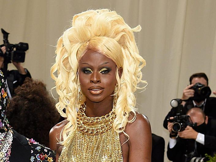 Symone at the met gala on the right wearing a gold gown.