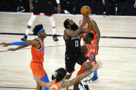 Houston Rockets' James Harden (13) goes up for a shot as Oklahoma City Thunder's Dennis Schroder (17) and Shai Gilgeous-Alexander, left, defend during the second half of an NBA basketball first round playoff game Saturday, Aug. 29, 2020, in Lake Buena Vista, Fla. (AP Photo/Ashley Landis)