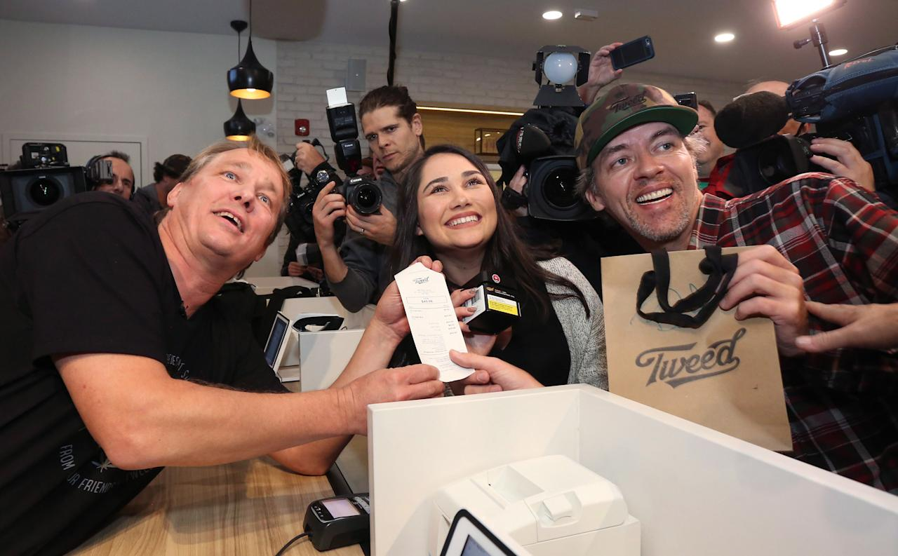 <p>Canopy Growth Corporation CEO Bruce Linton, left to right, poses with the receipt for the first legal cannabis for recreation use sold in Canada to Nikki Rose and Ian Power at the Tweed shop on Water Street in St. John's N.L. at 12:01 am NDT on Wednesday October 17, 2018.<br />(Photo from Paul Daly, The Canadian Press) </p>