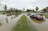 FILE - In this Tuesday, Aug. 21, 2018, file photo, vehicles are stalled on a flooded area of Greenway Boulevard after record rainfall Monday in Middleton, Wis. Officials in Dane County say this week's flooding caused more than $100 million in damage. (Amber Arnold/Wisconsin State Journal via AP, File)