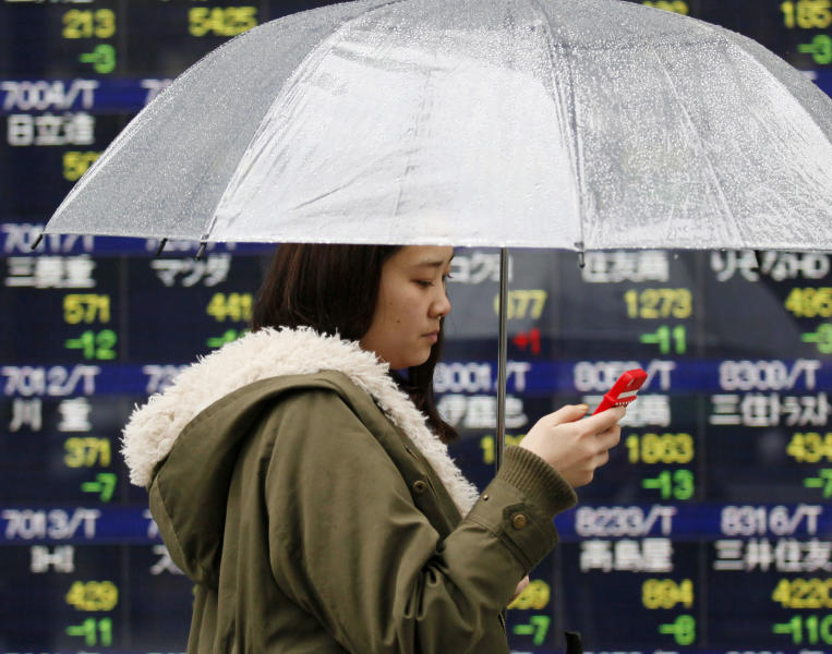 A woman walks by an electronic stock board of a securities firm in Tokyo, Thursday, March 20, 2014. Asian stocks inched down Thursday after comments from the new head of the Federal Reserve suggested U.S. interest rates could rise sooner than financial markets were anticipating. (AP Photo/Koji Sasahara)