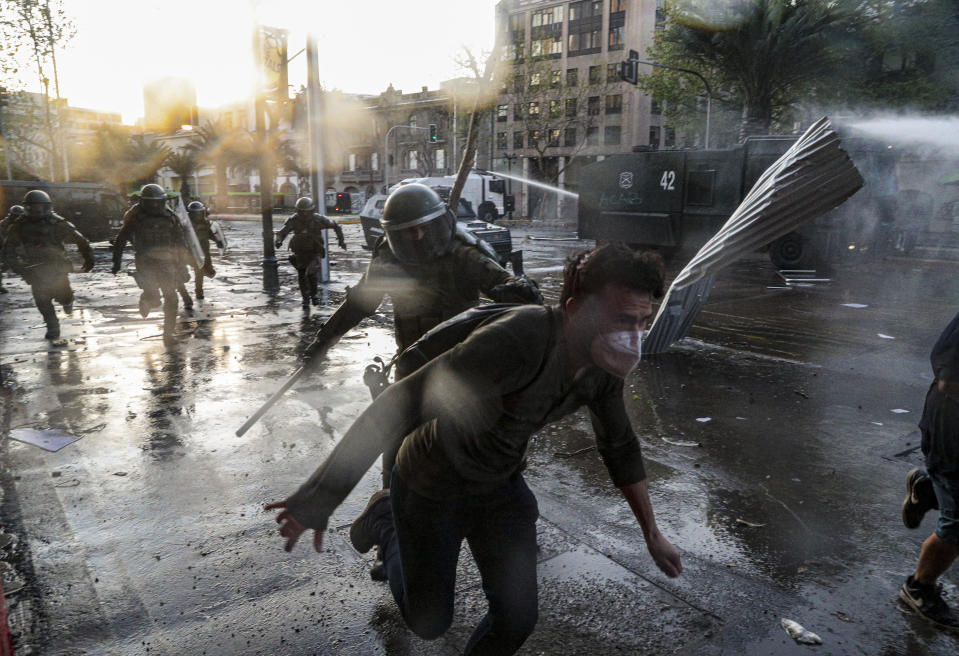 A demonstrator runs away from police during clashes at a protest against police in reaction to a video that appears to show an officer pushing a youth off a bridge the previous day at a protest, in Santiago, Chile, Saturday, Oct. 3, 2020. (AP Photo/Esteban Felix)