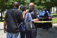 A police officer talks with two bystanders, Tuesday, July 9, 2019, in Cleveland. Police investigating the shooting death of a man in a vacant lot say they also found the bodies of a woman and two children in a nearby house. Authorities aren't saying how the three found inside the house Tuesday died, but they did say the four deaths are connected. (AP Photo/David Dermer)