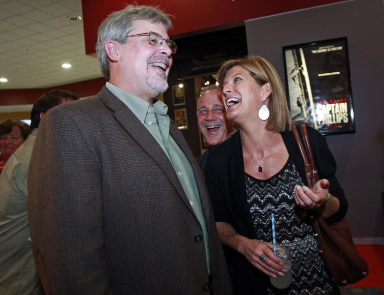 """Captain Richard Phillips, the real-life ship captain being played by Tom Hanks in the docudrama """"Captain Phillips,"""" left, enjoys a laugh with Darlene Durett before a screening of """"Captain Phillips,"""" on Tuesday, Oct. 1, 2013 in Williston, Vt. The film was adapted from the captain's memoir about the 2009 hijacking of his vessel by Somali pirates. Phillips spent five days as a hostage of the pirates on a lifeboat, where he was beaten, tied up and threatened before he was rescued days later by U.S. Navy SEALs. (AP Photo/Toby Talbot)"""