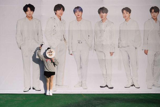 PHOTO: In this Oct. 29, 2019, photo, a fan of South Korea's BTS K-pop group poses against a backdrop featuring an image of the band members as they arrive for the final concert of their world tour at the Olympic stadium in Seoul. (Ed Jones/AFP via Getty Images)