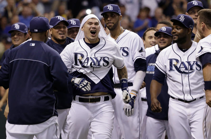 Tampa Bay Rays' Jose Lobaton, center, celebrates with his teammates after hitting the game winning home run in the ninth inning in Game 3 of an American League baseball division series against the Boston Red Sox, Monday, Oct. 7, 2013, in St. Petersburg, Fla. The Tampa Bay Rays won 5-4. (AP Photo/Chris O'Meara)