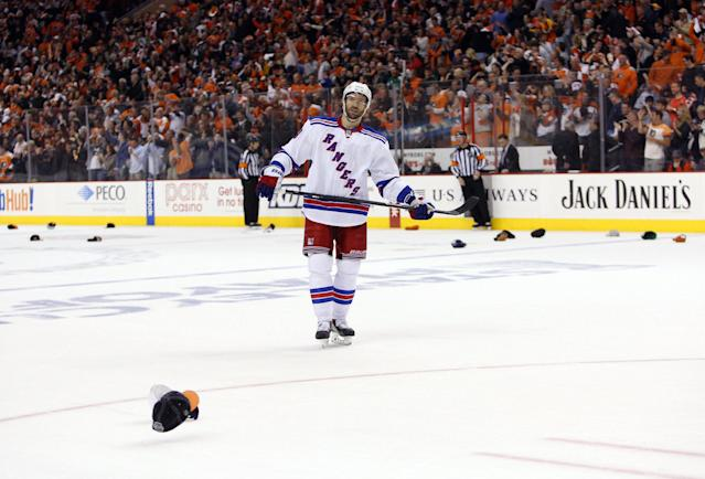 New York Rangers' Dominic Moore skates around the ice as fans throw hats for Philadelphia Flyers' Wayne Simmonds after Simmonds' hat trick during the second period in Game 6 of an NHL hockey first-round playoff series, Tuesday, April 29, 2014, in Philadelphia. (AP Photo/Chris Szagola)