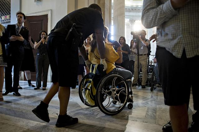 <p>A demonstrator in a wheelchair protesting cuts to Medicaid is led from the office of Senate Majority Leader Mitch McConnell by a U.S. Capitol police officer at the Russell Senate Office building in Washington on Thursday, June 22, 2017. (Photo: Andrew Harrer/Bloomberg via Getty Images </p>
