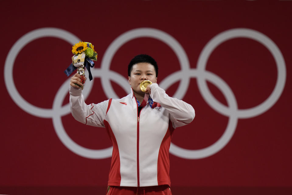 Wang Zhouyu of China celebrates on the podium after receiving the gold medal in the women's 87kg weightlifting event at the 2020 Summer Olympics, Monday, Aug. 2, 2021, in Tokyo, Japan. (AP Photo/Luca Bruno)