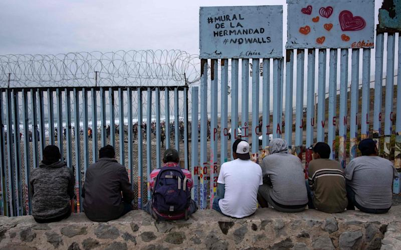 Migrants at the US-Mexico border in Tijuana - AFP