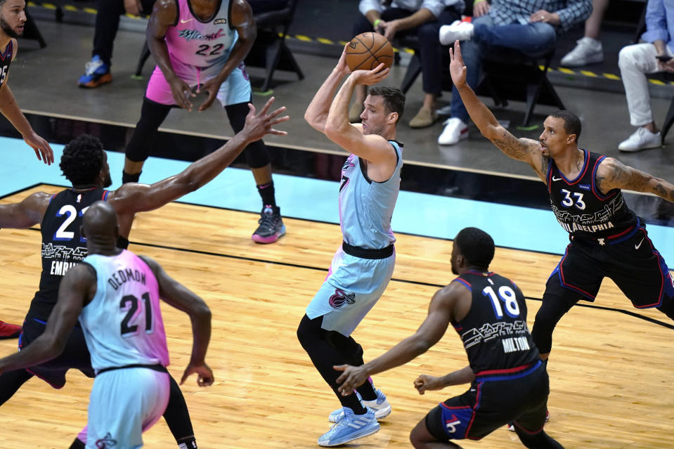 Miami Heat guard Goran Dragic, center, is defended by Philadelphia 76ers center Joel Embiid, left, guard Shake Milton (18) and guard George Hill (33) during the first half of an NBA basketball game Thursday, May 13, 2021, in Miami. (AP Photo/Lynne Sladky)