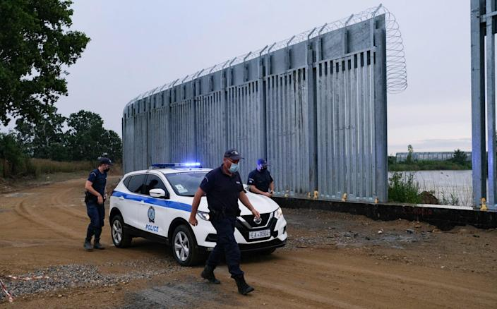 Greek police patrol a new 5-metre steel fence installed along the Evros River by the border with Turkey - Byron Smith /Getty Images Europe