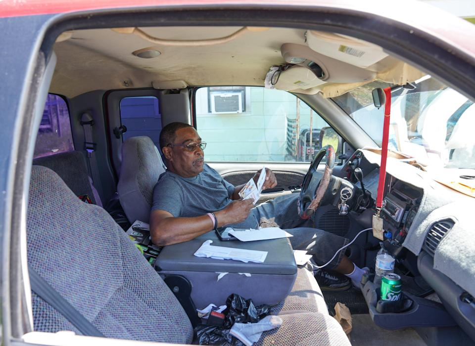 Ernest Benedict Holland, 64, leafs through bills while trying to stay cool inside his pickup after losing power at his home in Reserve, Louisiana, following Hurricane Ida.