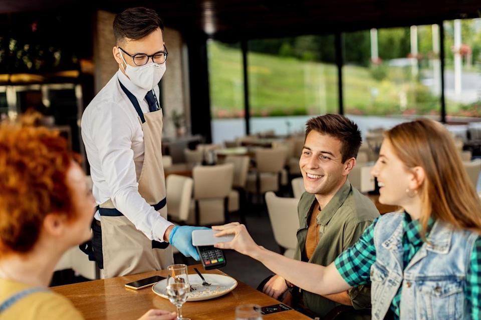 Group of friends paying contactless with mobile phone to a waiter in a cafe.