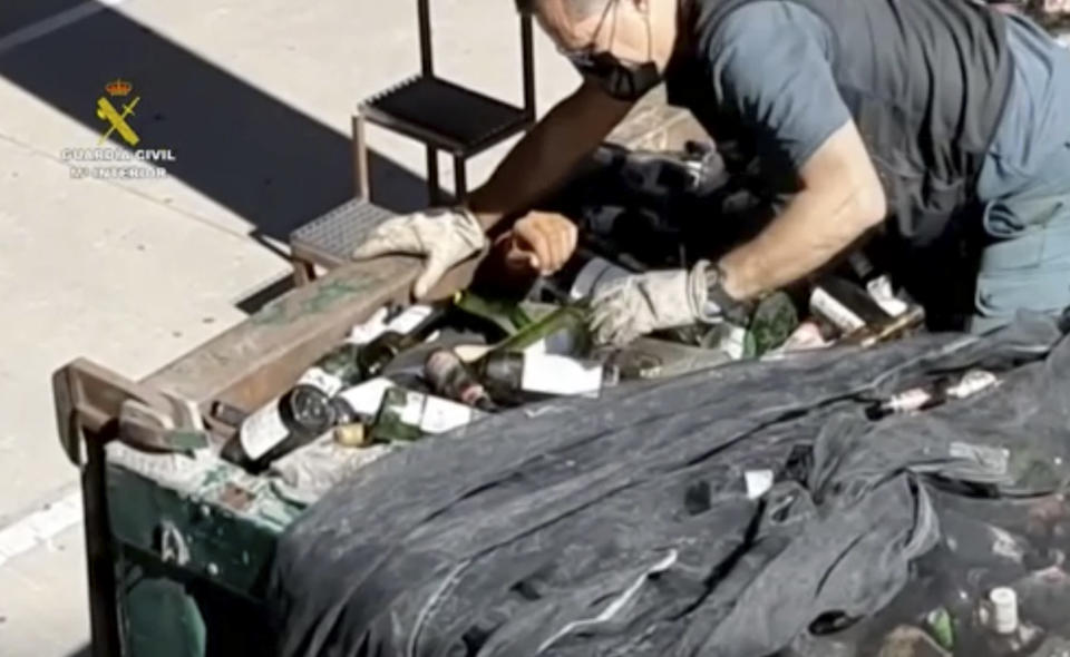 In this image taken from video made available by the Guardia Civil, an officer of the Guardia Civil helps a man out from under glass bottles in a container in Melilla, Spain, Friday Feb. 19, 2021. Spanish authorities say they have found and rescued 41 migrants who tried to reach continental Europe from North Africa in the past four days, some of them hiding inside a container of discarded glass bottles and a bag of toxic ash. (Guardia Civil via AP)