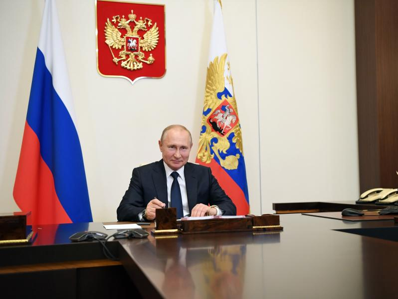 Russian President Vladimir Putin, smiles during a meeting via teleconference at the Novo-Ogaryovo residence outside Moscow, Russia, Monday, June 1, 2020. Putin set a nationwide vote on constitutional amendments allowing him to extend his rule for July 1. (Alexei Nikolsky, Sputnik, Kremlin Pool Photo via AP)