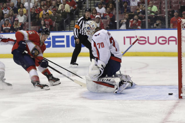Florida Panthers center Frank Vatrano, left, scores a goal against Washington Capitals goaltender Braden Holtby (70) during the first period of an an NHL hockey game, Thursday, Nov. 7, 2019, in Sunrise, Fla. (AP Photo/Lynne Sladky)
