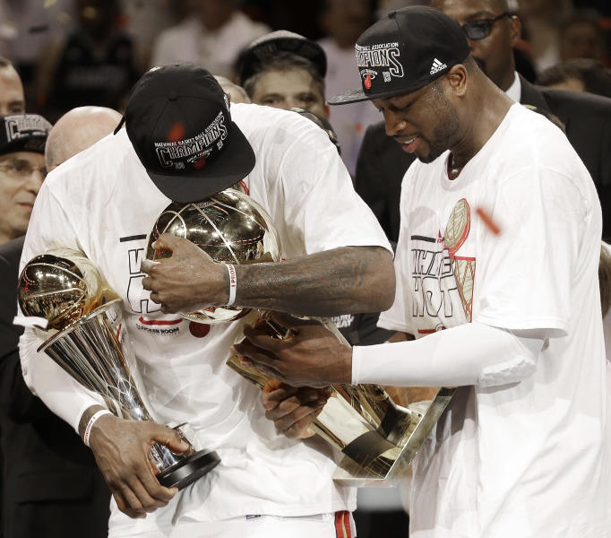 The Miami Heat's Dwyane Wade, right, holds the Larry O'Brien NBA Championship Trophy with LeBron James holding his Bill Russell NBA Finals Most Valuable Player Award after Game 7 of the NBA basketball championship game against the San Antonio Spurs, Friday, June 21, 2013, in Miami. The Miami Heat defeated the San Antonio Spurs 95-88 to win their second straight NBA championship. (AP Photo/Lynne Sladky)