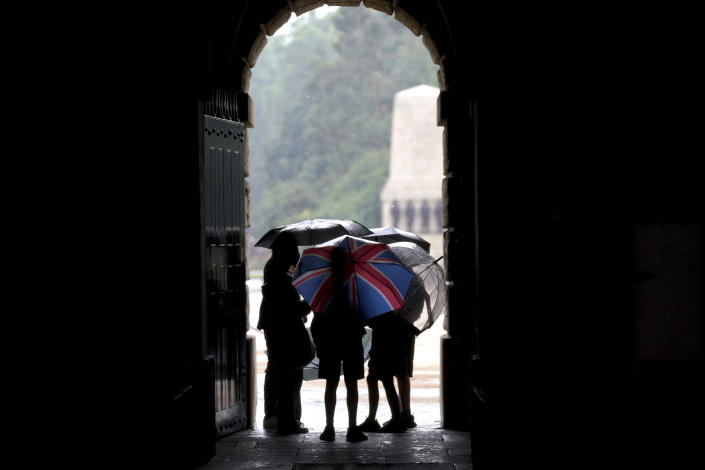 A group of people take shelter in Horse Guards Parade in central London, Sunday July 25, 2021. Thunderstorms bringing lightning and torrential rain to the south are set to continue until Monday it is forecast. (Victoria Jones/PA via AP)