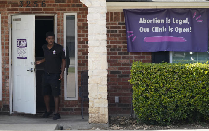 FILE - In this Sept. 1, 2021 file photo, a security guard opens the door to the Whole Women's Health Clinic in Fort Worth, Texas. Even before a strict abortion ban took effect in Texas this week, clinics in neighboring states were fielding more and more calls from women desperate for options. The Texas law, allowed to stand in a decision Thursday, Sept. 2, 2021 by the U.S. Supreme Court, bans abortions after a fetal heartbeat can be detected, typically around six weeks. (AP Photo/LM Otero)