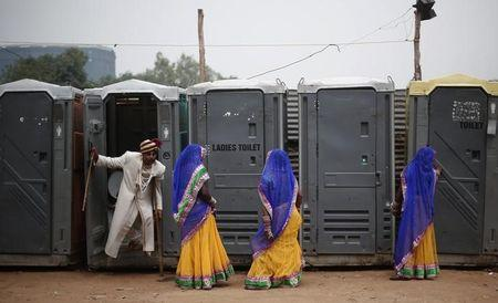 A groom comes out from a toilet as brides stand at the venue for a mass wedding ceremony at Ramlila ground in New Delhi