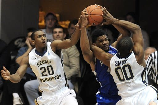 Saint Louis forward Dwayne Evans battles George Washington forward Dwayne Smith (00) and Lasen Kromah (20) for the rebound during the second half of their NCAA college basketball game, Saturday, March 2, 2013, in Washington. Saint Louis defeated George Washington 66-58. (AP Photo/Richard Lipski)