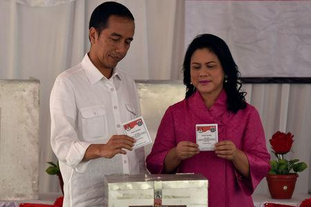 Indonesian President Joko Widodo and First Lady Iriana cast their ballots in the Jakarta governer election in Gambir, Jakarta