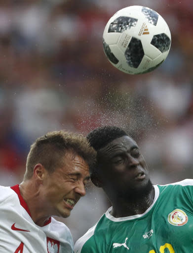 Poland's Thiago Cionek, left, and Senegal's Alfred Ndiaye, right, go for a header during the group H match between Poland and Senegal at the 2018 soccer World Cup in the Spartak Stadium in Moscow, Russia, Tuesday, June 19, 2018. (AP Photo/Darko Vojinovic)