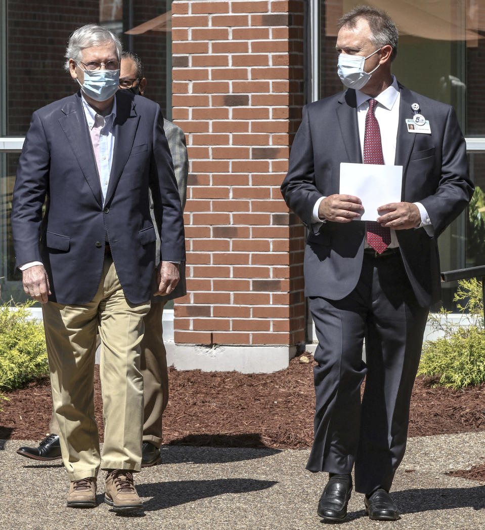 """FILE - In this July 14, 2020, file photo Senate Majority Leader Mitch McConnell of Ky., left, walks with Ed Heath, CEO of Owensboro Health Muhlenberg Community Hospital, before a press conference at the hospital in Greenville, Ky. """"It's not going to magically disappear,"""" said McConnell, during a visit to a hospital in his Kentucky home state to thank front-line workers. (Greg Eans/The Messenger-Inquirer via AP, File)"""