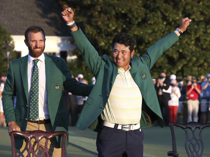 Hideki Matsuyama, of Japan, celebrates while wearing the champion's green jacket as Dustin Johnson looks on after winning the Masters golf tournament on Sunday, April 11, 2021, in Augusta, Ga. (Curtis Compton/Atlanta Journal-Constitution via AP)